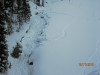 Foot pounding the snow in the enlarged creek under Wolverine