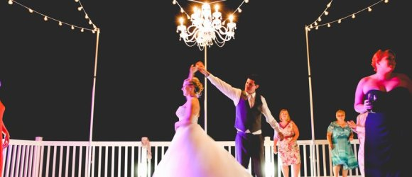 Ocean Isle Beach House wedding reception lighting with string edison chandelier and pool globes