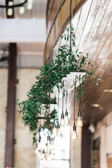 Long line of custom vintage handmade edison lights with greenery over head table