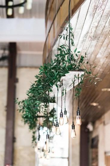 Long line of custom vintage handmade edison lights with greenery over head table