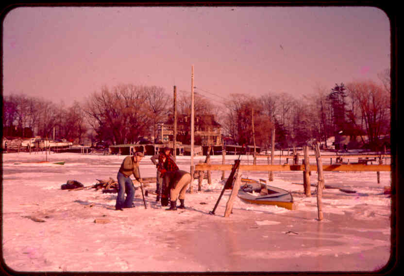 Digging boats out of the ice. See 2 story cottage on Clark Island