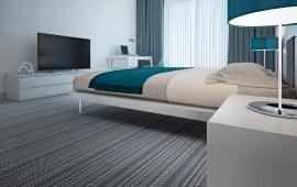Lindisfarne herringbone tufted carpet installed in a modern, minimalist hotel room.