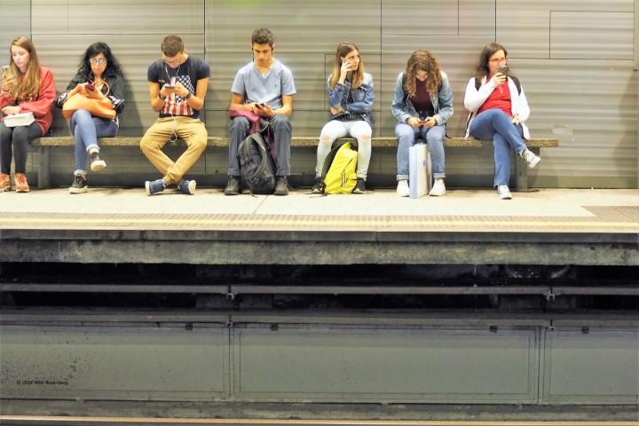 wachtende mensen met mobiel, metro Milaan