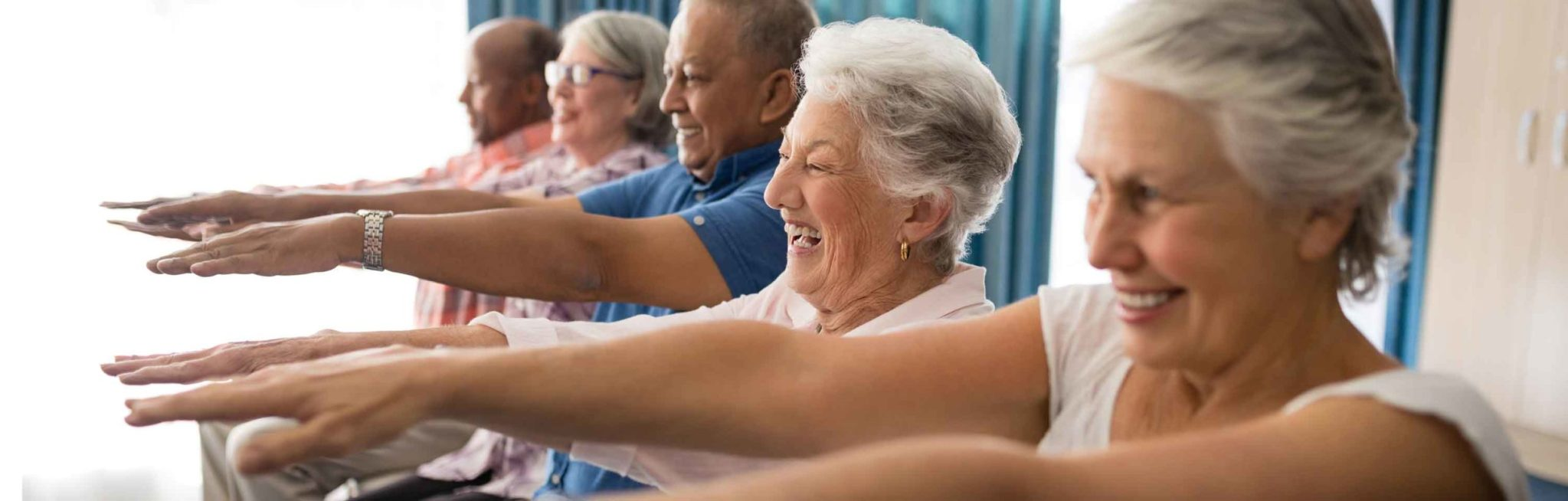 A group of seniors taking part in an exercise class, just one of the premium amenities and activities offered by Winchester Glen Retirement Community.