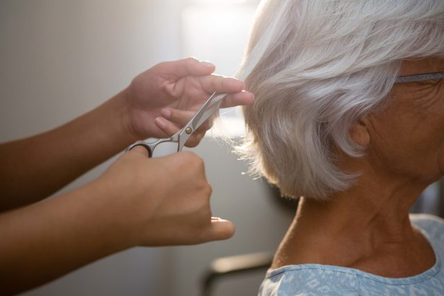 An elderly lady gets her hair trimmed at the salon and spa.