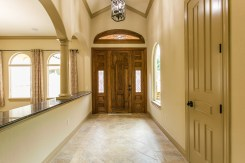Beautiful wood front door and nautral stone floor in the foyer, with views into the formal dining and living areas.