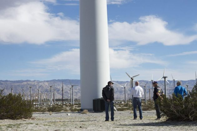 Tour-goers stand near the base of a new wind turbine.