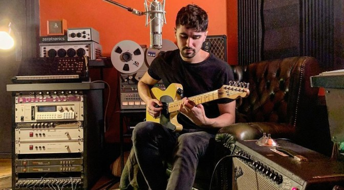Danny Addison playing guitar in the studio