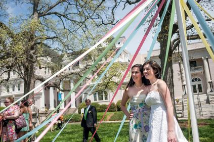 "Tami Lee, Brenau University's director of special events, poses for a picture with her Alpha Chi Omega sorority sister and the 2013 May Queen Eleanor Kahn under the May Pole on the front lawn of the Gainesville campus. Lee offered her wedding dress to Kahn to use in the ceremony after Kahn expressed a concern about affording a wedding dress to use in the ceremony when Lee was encourageing her to run for May Queen. ""Once she was elected we tried it on and it just fit perfectly,"" Lee said."