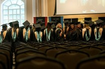 Students wave to family and friends before the start of the undergraduate and graduate commencement services Saturday in the banquet hall of the First Baptist Church in Gainesville.