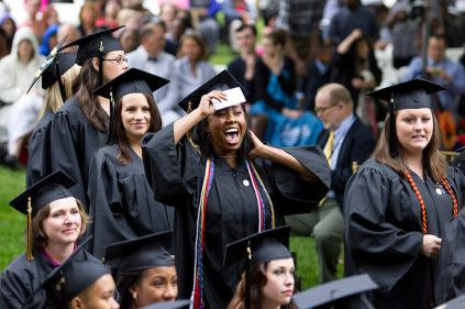 Mycharia Spurling cheers as the 2013 Women's College graduates walk across the stage on the front lawn of the Gainesville campus.
