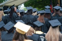 Adrienne Reed, left, waves to the crowd of friends and family that came out to support their graduating seniors in the rainy weather Friday.