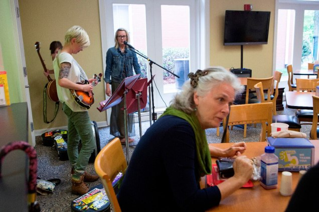 Jordan Wallace, left, tunes her mandolin as Barbara Steinhaus, right speaks with her colleagues before the start of the Bluegrass and Books event in the Tea Room on Brenau's Gainesville campus.
