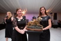 Brenau University students Casey Wyatt, left, and Amber Boyd show off a maquette of the bronze tiger statue, Lucile, during the live auction at the Brenau Gala.