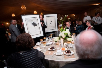 Brenau facilities staff members carry artwork around for guests to see during the live auction at the Brenau Gala.