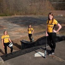 Brenau softball players, from left, Cheyenne Marsh, Mackenzie Oliver and Jenny Shepherd stand on the future site of the Brenau University Athletic Complex next to the Milliken plant in Gainesville, Ga.