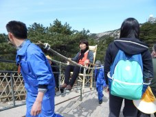 In this photo, a tired visitor is carried up the trail at Huangshan in a sedan chair. There was a cable car system to carry visitors most of the way to the top, but manpower was the only method for moving supplies and often people from the cable car station to the facilities and high peaks of the park. Porters carrying impossible-seeming loads on their shoulders with yokes were a common sight along the trails on the mountain.
