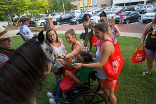 "Chelsey Bell, center, pets a mustang on the Downtown Gainesville square during ""Tiger Takeover."""