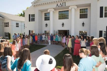Members of Alpha Delta Pi stand locked in arms singing on the lawn during Sorority Open House.