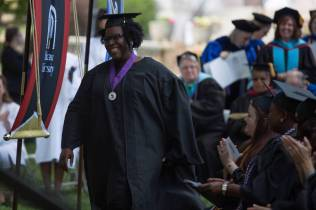 Portia Burns walks to the stage to accept one of two Outstanding Part-Time Faculty Awards during The Women's College commencement on Friday, May 6, 2016, in Gainesville, Ga. (AJ Reynolds/Brenau University)