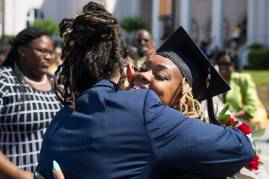 Kia Howell, an early childhood education graduate, gets a hug after the Brenau University Undergraduate and Graduate Commencement on Saturday, May 7, 2016, in Gainesville, Ga. (AJ Reynolds/Brenau University)