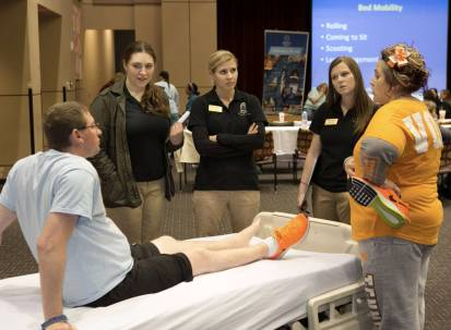 Former Shepherd Center patient Toy Wix, far left, and his wife Spencer, far right, talk with Brenau University occupational therapy graduate students Victoria Kotkiewicz, from left, Julia Zametin & Callie Setzer about techniques to help people living with impairments and disabilities. Students got a chance to practice what they were taught during hands on labs at the Atlanta center that specializes in spinal cord & brain injury rehabilitation. (Phil Skinner for Brenau University)