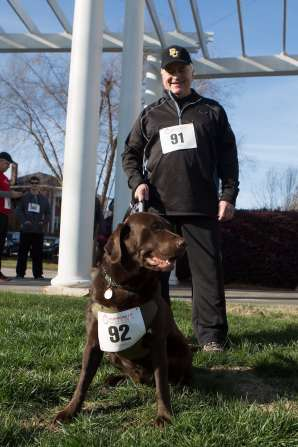 Brenau President Ed Schrader and his chocolate lab Jake during the Dempsey Dash 5K, a race celebrating the memory of Brenau's longtime Executive Vice President and CFO Wayne Dempsey, on Saturday, March 11, 2017. (AJ Reynolds/Brenau University)