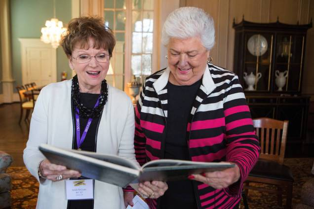 Sarah McCrary, WC '67, and her former instructor Janis Wilson look at a Bubbles 1967 yearbook during an afternoon tea for the Women's College Class of 1967. (AJ Reynolds/Brenau University)