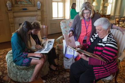 Allie Smith, a senior mass communications major, Sarah McCrary, WC '67, Ann Leathers Dyal, WC '67, and Janis Wilson look at Bubbles yearbooks inside the Lockett Mitchell Parlor. (AJ Reynolds/Brenau University)