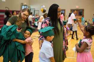 Olivia McFerrin, a senior early childhood education major, left, gets a hug from a student while Sasha Stovall, WC '15, during the commencement ceremony for the RISE Program on Friday, July 14, 2017 at Fair Street School. (AJ Reynolds/Brenau University)