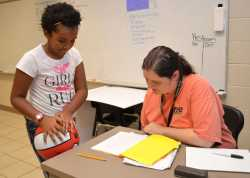 Aalliyah Glasper, left, discusses a story she wrote with her teacher in the RISE Summer Program, Bri Neves.