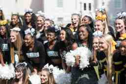 Terry Capers, BU '14 and winner of the Service to Brenau Award, poses for photos with a group of cheerleaders during the homecoming celebrations at Brenau University. (AJ Reynolds/Brenau University)