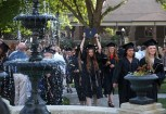 A graduate celebrates with her diploma as the graduates walk toward the fountain at the conclusion of the Women's College Commencement at Brenau University Friday May 4, 2018 in Gainesville, Ga. (Jason Getz for Brenau University)