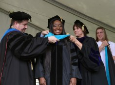 Brenau University Provost James Eck, left, and Chair of the Physical Therapy Department Kathye Light fixes the academic regalia of Keisha Cooper as she receives her doctorate in physical therapy during the graduate and undergraduate commencement Saturday May 5, 2018 in Gainesville, Ga. (Jason Getz for Brenau University)