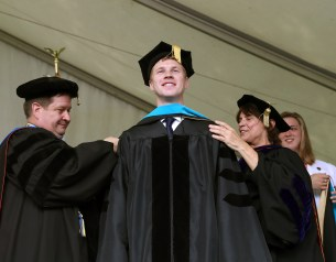 Brenau University Provost James Eck, left, and Chair of the Physical Therapy Department Kathye Light fixes the academic regalia of Steven Hightshue as he receives his doctorate in physical therapy during the graduate and undergraduate commencement Saturday May 5, 2018 in Gainesville, Ga. (Jason Getz for Brenau University)