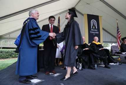 An ANU-Brenau University student receives her diploma from Brenau University President Ed Schrader, left, and ANU Provost Duanming Zhou, center, during graduate and undergraduate commencement Saturday May 5, 2018 in Gainesville, Ga. (Jason Getz for Brenau University)