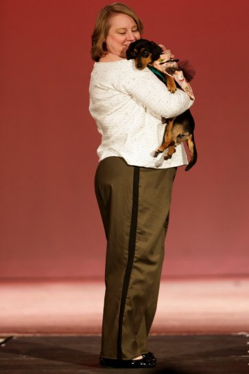 Rosanne Short holds an adoptable dog from the humane society in the Elegant Kleidung portion of the Collections 2018 fashion show. (AJ Reynolds/Brenau University)
