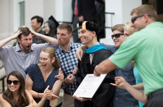 Ryan Ahlenius (center), the first graduate from Brenau University with a Doctor of Physical Therapy, jokes with friends following the 2018 Spring Commencement Ceremony on Saturday, May 5, on Brenau University's historic Gainesville campus. (Nick Bowman for Brenau University)