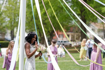 May Queen Gloria Clark waves from under the maypole.