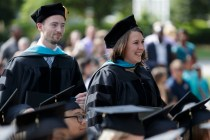 Students stand during commencement ceremony.