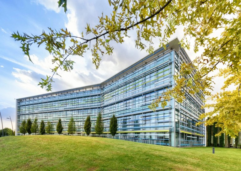 exterior of a modern angular glass fronted office building in a spring landscape with green lawns and trees under a blue cloudy sky