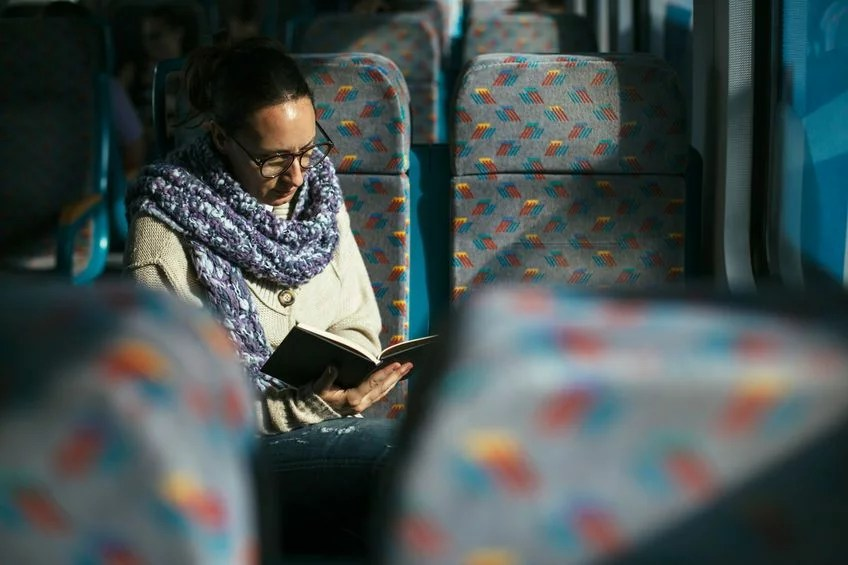33657669 - woman reading book on train bus