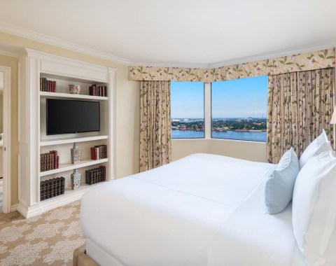The bedroom of the Windsor Court Hotel's Presidential Suite, featuring a king size bed, tv, and view of the Mississippi River