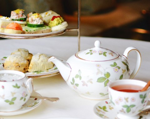 Table setup for English afternoon tea service including teapot, scones, tea sandwiches and teacups
