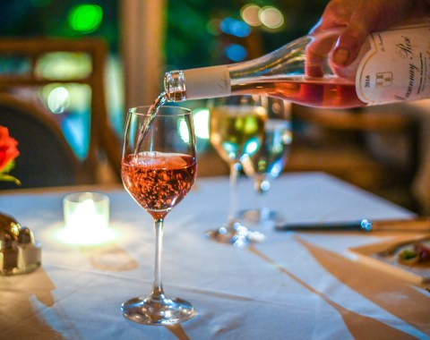 A glass of Rosé being poured at a table set for a candlight dinner at the Windsor Court Hotel