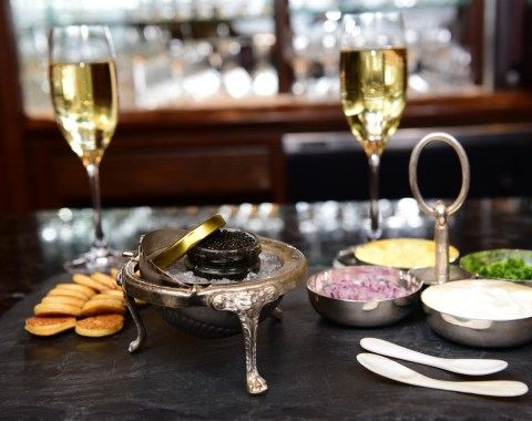 Caviar display including mother of pearl spoons, glasses of sparkling wine, and other accoutrements