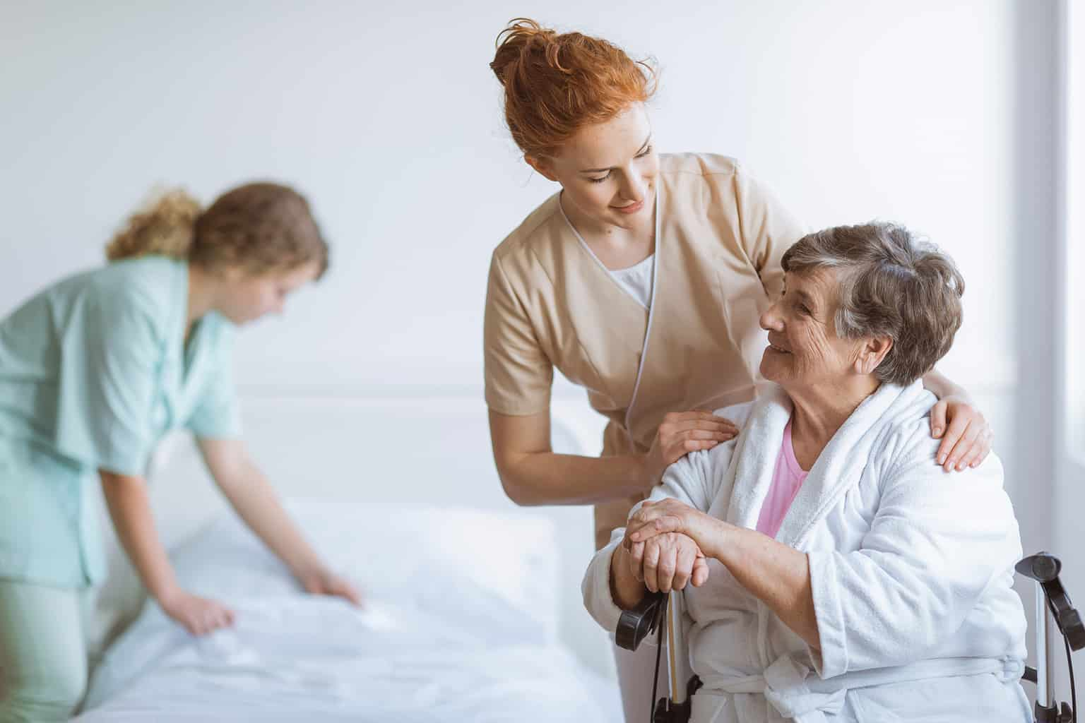 Nurses assisting an elderly woman in a wheelchair