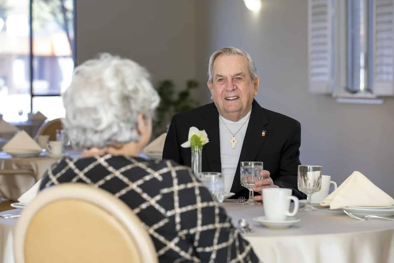 Senior man smiling at dining table