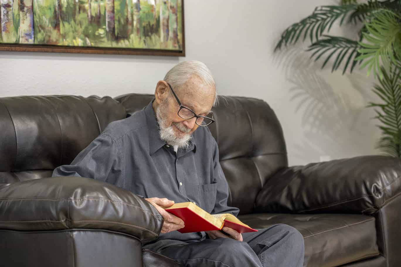 Senior man on couch reading book