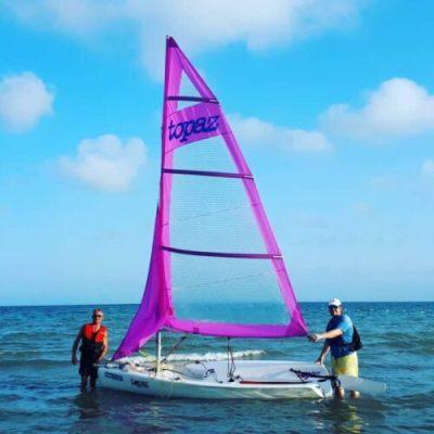 Dos hombres sosteniendo el barco de vela ligera a orillas del mar en la escuela náutica